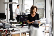 Businesswoman Using Digital Tablet With Colleague Standing In Background At Open Plan Office