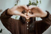 Girl In Warm Clothing Showing Heart Shape With Hand At Home
