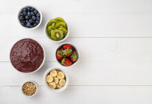 Brazilian Typical Acai Bowl With Fruits And Muesli Over Wooden Background With Copy Space