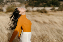 Carefree Young Woman With Eyes Closed Standing In Field During Windy Day