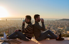 Gay Couple Drinking Coffee While Sitting Back To Back On Observation Point At Bunkers Del Carmel, Barcelona, Spain