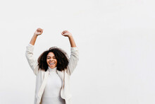 Cheerful Afro Woman With Arms Raised Screaming While Standing Against White Wall