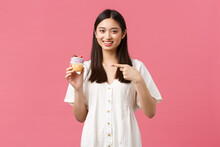Food, Cafe And Restaurants, Summer Lifestyle Concept. Happy Asian Woman Satisfied With Awesome Taste Of Dessert, Pointing At Cupcake Recommend Bakery Shop, Standing Pink Background