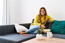 Woman With With Long Hair With A Remote Control In Hand Having Fun At Home