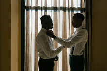 Side View Of Black Man Adjusting Bow Tie For Groom While Standing In Room On Wedding Day And Preparing For Ceremony