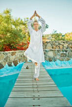 Blond Male Hipster Yogi In White Clothes Standing In Tree Pose Near Tibetan Singing Bowl And Crystals On Wooden Path Bridge On Top Of A Turquoise Pool In Tropical Garden During Yoga Retreat