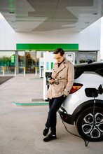 Male Entrepreneur In Stylish Outfit Standing At Petrol Station And Browsing Mobile Phone While Standing Near Car With Fuel Nozzle