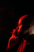 Side View Of Male Rocker With Bald Head Smoking And Exhaling Fume In Dark Studio With Red Neon Light On Black Background