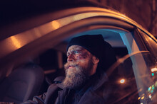 Hipster Man With Beard And Cinema Makeup Driving A Car