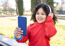 Happy Ethnic Child With Afro Hairstyle Enjoying Songs In Headphones While Using Smartphone In Urban Park