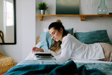 Girl Lying In Bed Reading A Book