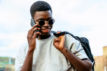 Young African American Man With Backpack And Fashionable Sunglasses Talking On A Cell Phone Under A Cloudy Sky.