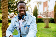 Young Black Male In Denim Jacket With Headset On Green Meadow In City
