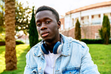 Young Black Male In Denim Jacket With Headset Looking At Camera On Green Meadow In City