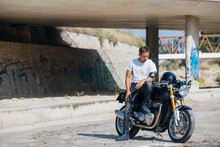 Stylish Male Biker Sitting On Modern Motorcycle In Urban Area And Looking Down