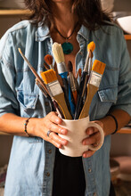 Cropped Unrecognizable Female Master In Casual Clothes Smiling And Looking At Camera While Standing Near Shelf In Workshop With Mug Of Various Paintbrushes In Hand