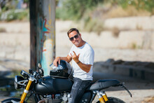 Stylish Male Biker Sitting On Modern Motorcycle In Urban Area And Looking At Camera