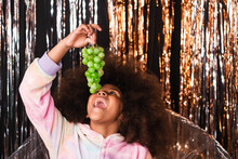 Cheerful Black Girl With Curly Hair Eating Sweet Green Grapes While Sitting In Studio On Background Of Shiny Tinsel Stripes