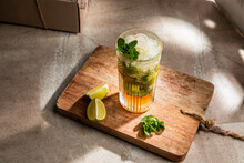 From Above Of Refreshing Cold Alcoholic Mojito With Ice Mint Leaves And Cut Lime On Wooden Board