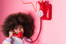 Smiling Ethnic Girl With Afro Hairstyle Talking On Old Fashioned Red Telephone In Studio And Looking At Camera On Pink Background