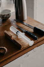 From Above Of Various Sharp Knives And Culinary Syringe Placed On Wooden Cutting Board In Kitchen