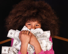 Cheerful Wealthy African American Teenage Girl With Heap Of Dollar Bills Looking At Camera