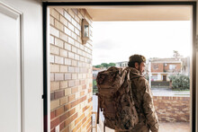 Back View Of Male Soldier With Backpack And In Military Uniform Standing At Doorway Before Departure