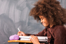 Side View Of Clever Teenage African American Girl Sitting At Table In Classroom With Blackboard During Lesson At School