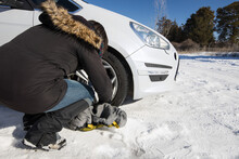 Side View Of Anonymous Female Driver Changing Wheel Of Car In Winter