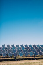 Modern Solar Panels Installed In Field Against Cloudless Blue Sky In Photovoltaic Power Station