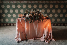 Blooming Flowers On Tablecloth With Number And Burning Candles Against Ornamental Wall During Festive Event In Cafeteria