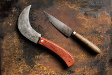 Top View Of Sharp Knives With Shabby Blades Placed On Rusty Metal Table