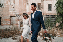 Young Glad Multiracial Groom And Bride Holding Hands Strolling On Walkway Against Aged Construction On Wedding Day