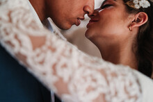 Side View Of Cropped Unrecognizable Romantic Ethnic Newlywed Couple In Elegant Clothes Bonding Tenderly With Eyes Closed In Light Wedding Studio