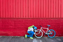 Side View Of Unrecognizable Hipster Man Fixing Wheel Of Modern Bike On Colorful Red Wall On The Street