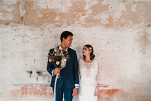 Young Smiling Multiracial Groom With Bridal Bouquet Holding Beloved By Hand While Looking At Each Other Near Old Wall