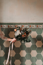 Crop Anonymous Woman With Blooming Flowers And Ribbon Near Tiled Wall With Decor On Wedding Day In Building