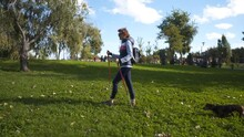 Caucasian Thin Elderly Woman Active Leisure Scandinavian Walking With Sticks And Dachshund Dog In City Park, Sunny Weather. Active Senior Female Practicing Nordic Walking With Poles Outdoors With Pet