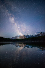 The Milky Way Reflecting Off Of The Calm Waters Of Herbert Lake While The Town Of Lake Louise Illuminated The Canadian Rockies.