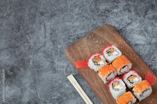 Fototapeta Sushi maki with red caviar and cream cheese on a wooden board obraz