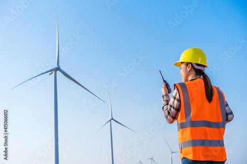 Fototapeta female engineer using walkie talkie to checking system against wind turbine farm obraz
