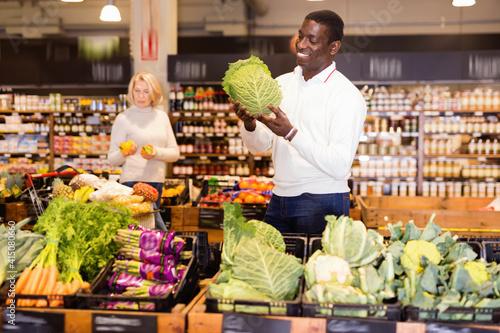 Fototapeta Portrait of positive cheerful adult African man buying fresh organic vegetables in supermarket obraz