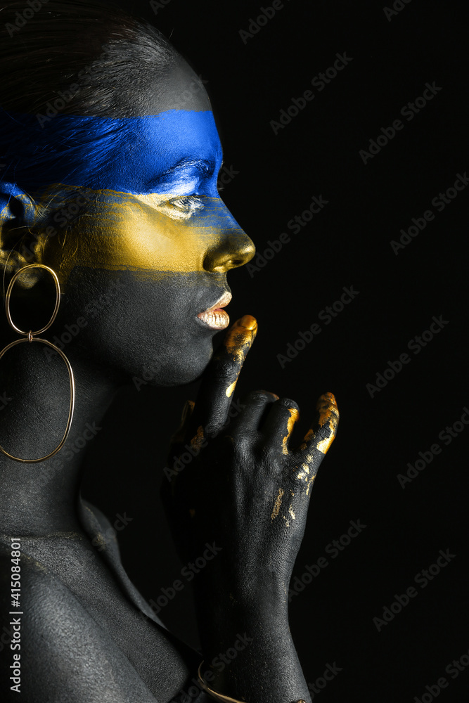 Fototapeta Young Ukrainian woman with blue and yellow paint on her body against dark background