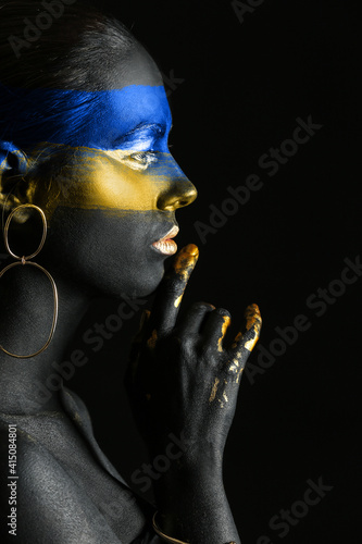 Young Ukrainian woman with blue and yellow paint on her body against dark background © Pixel-Shot