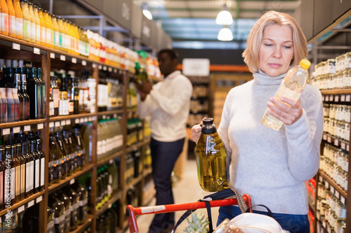 Fototapeta Portrait of thoughtful cheerful glad mature woman looking for vegetable oil in g