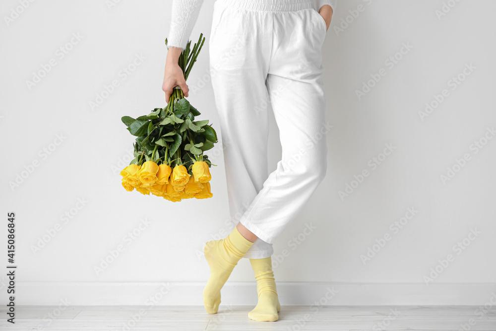 Fototapeta Young woman with beautiful yellow roses near light wall