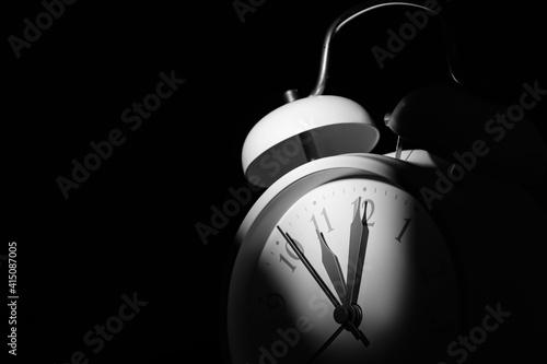 Photographie Alarm clock on black background, closeup