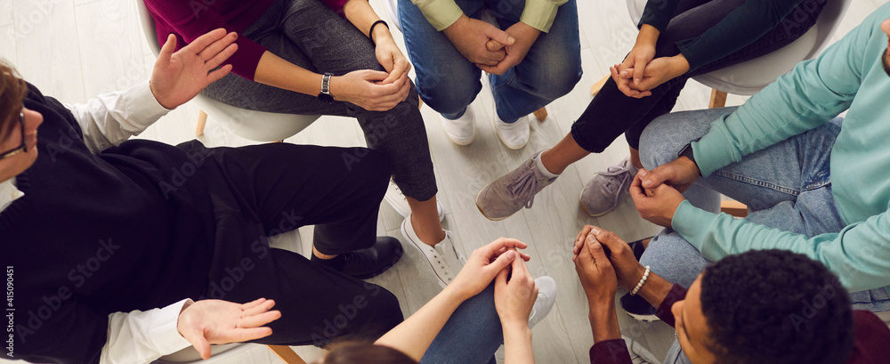Fototapeta Top view of diverse people sitting in a close circle and talking to a therapist. Cropped image of unidentified people receive help and support during a group therapy session. Concept of group therapy.