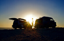 Silhouette Of Friends And Parked Campervans Close To The Beach. Surf And Travel Concept. Van Life. Travel With A Van.
