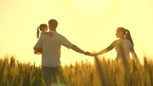 Healthy Mother, Father And Little Daughter Enjoying Nature Together, Outdoors. Happy Family Of Farmers With Child, Are Walking On A Wheat Field. Slow Motion. Mom, Dad And Child Walk Hand In Hand